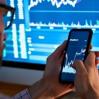 trader investor analyst using mobile phone app analytics for cryptocurrency