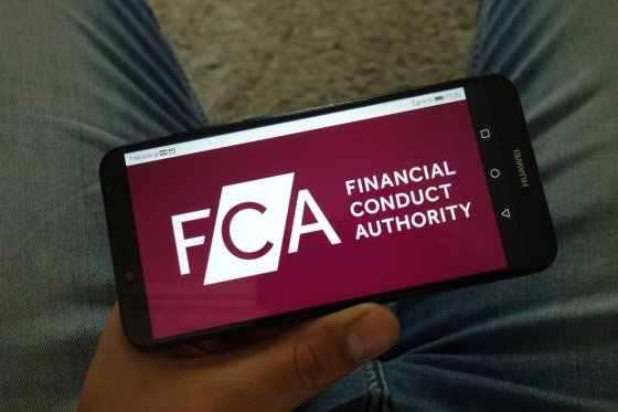 A mobile phone displays the UK Financial Conduct Authority's name and logo