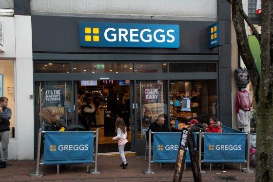 A UK high street showing a Greggs shop.