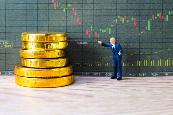 A figure of an executive stands beside a pile of coins in front of a data chart