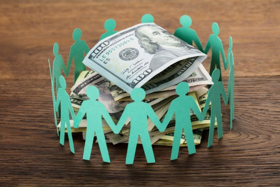 Paper people circled around a small pile of money