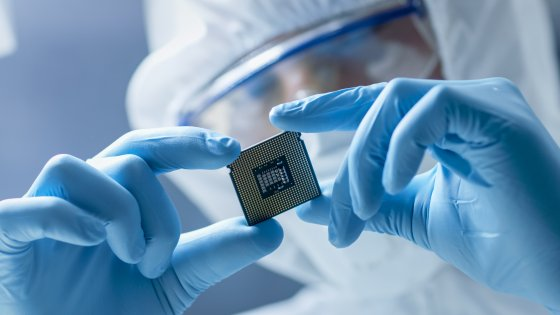 A masked and gloved person holds a semiconductor chip in a laboratory setting