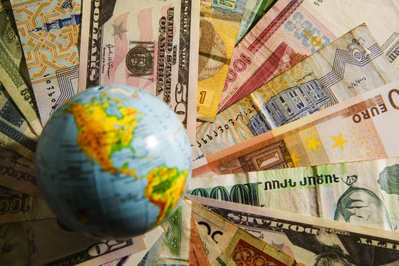A globe sits on top of a selection of world currencies