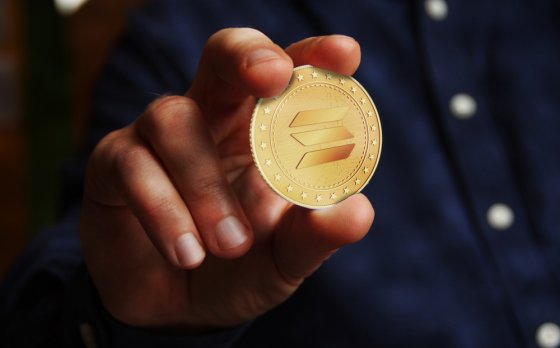 Solana altcoin cryptocurrency symbol golden coin in hand