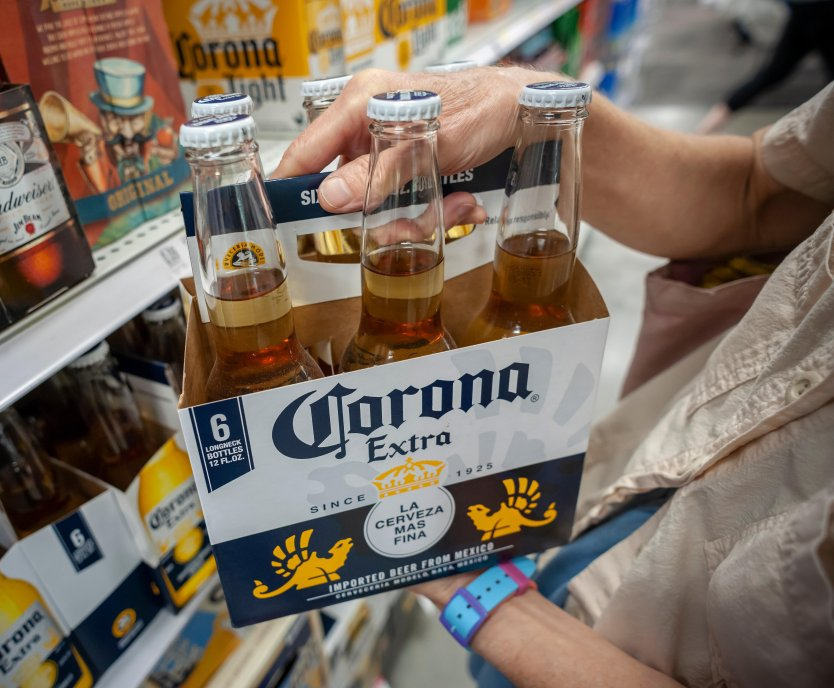 A shopper picks out a six-pack of Corona Extra, one of the products owned by Constellation Brands.