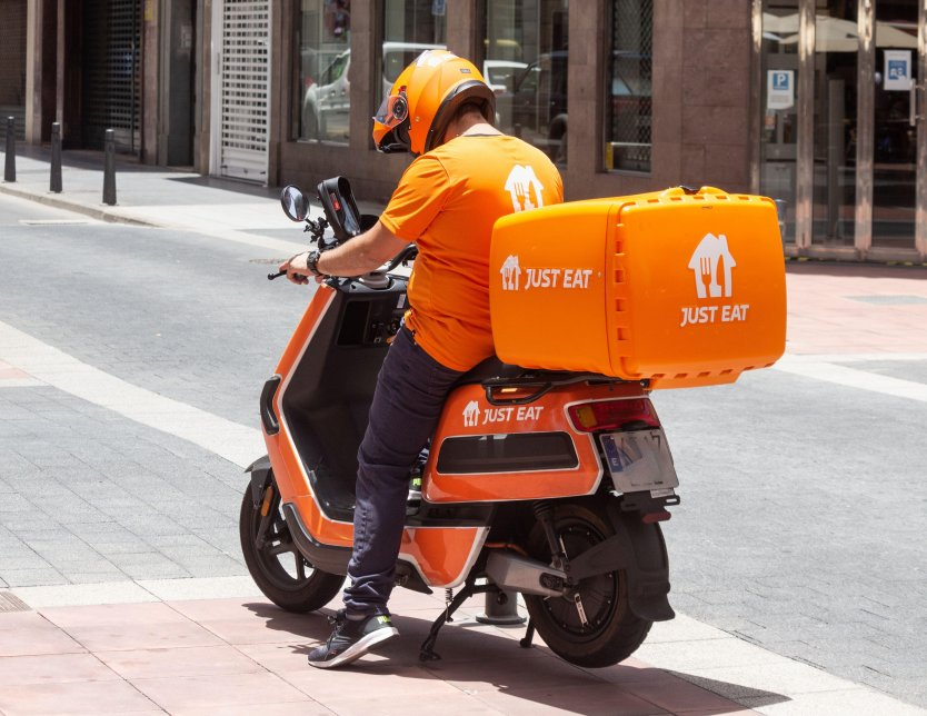 A delivery driver dressed in orange is sitting on a motorbike. He has delivery bag with the Just Eat logo on the back of his bike.