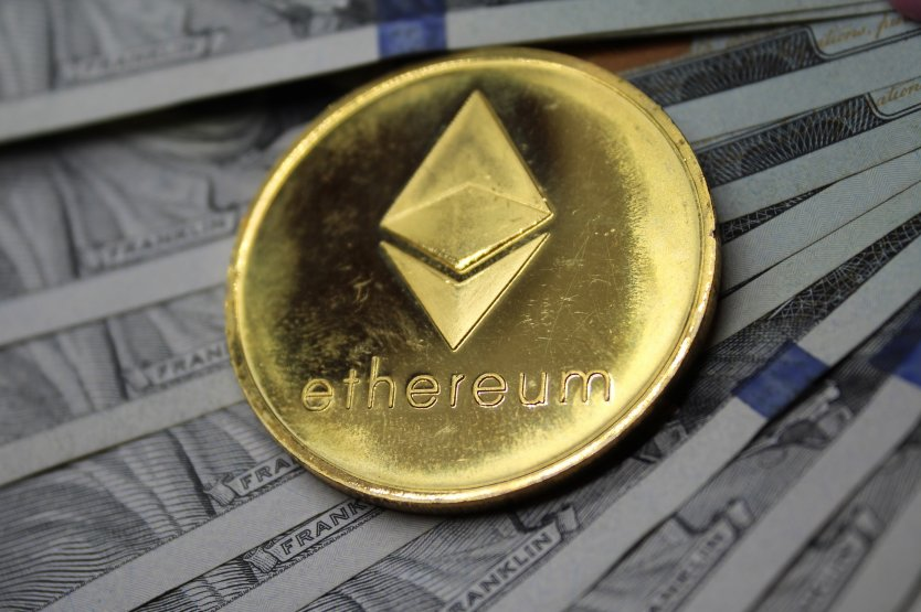 Gold ethereum coin on a background of US $100 notes