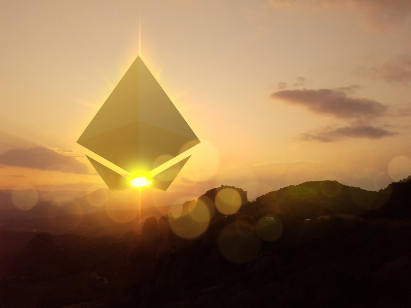 Ethereum symbol in the sky as the sun rises over mountains