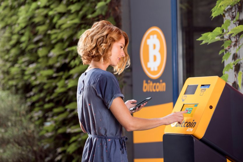 Woman in front of bitcoin ATM