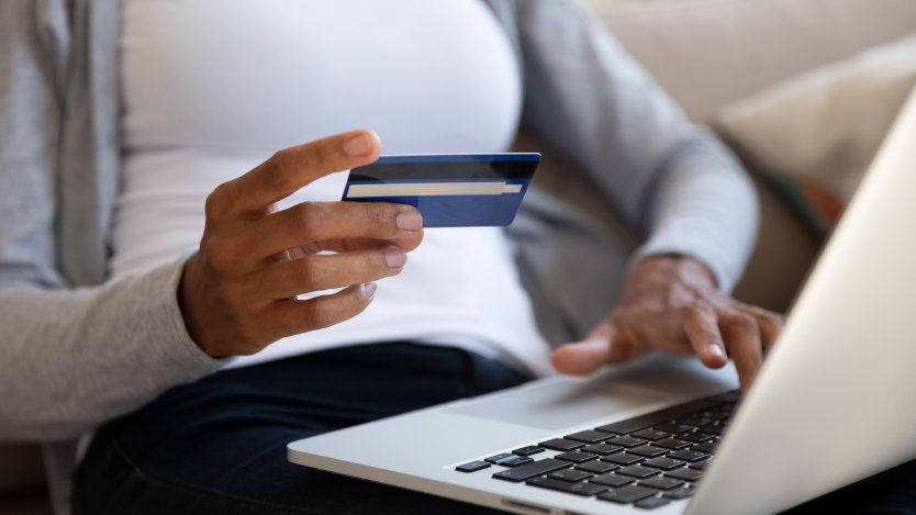 Woman holding a credit card while sitting at a laptop