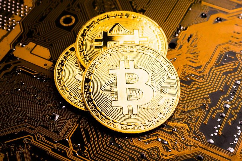 Bitcoin tokens gleam on an orange blockchain network background