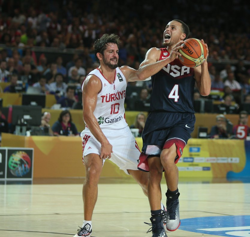 Basketball players Kerem Tunceri (left) and Stephen Curry during a game