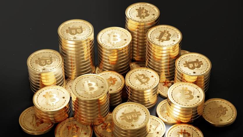 Several stacks of bitcoin tokens against a black background