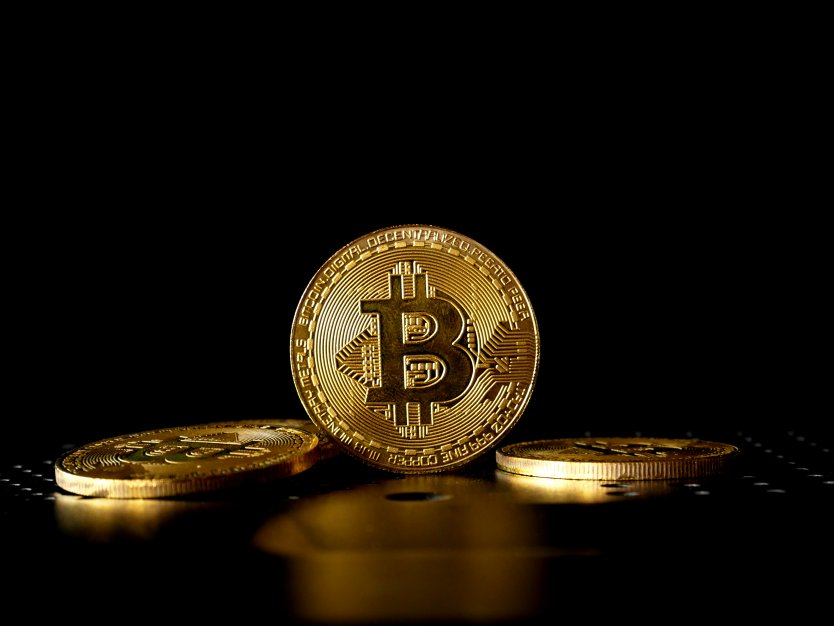 Cryptocurrency tokens with Bitcoin coin standing upright against a black background