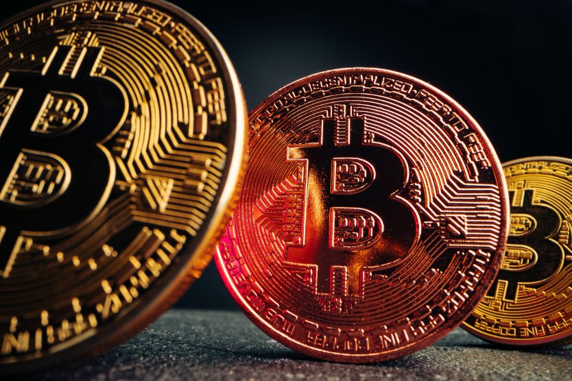 Three large bitcoin tokens in different shades against a black background