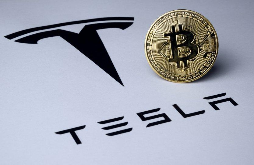 The Tesla badge on a car next to a conceptual bitcoin token
