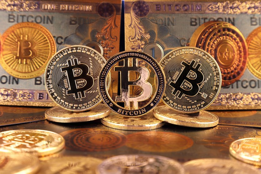 Tokens representing bitcoin stand on edge surrounded by more golden coins