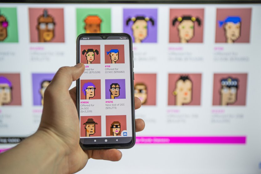 A person holds a smartphone over a series of cartoon graphics for use as NFTs