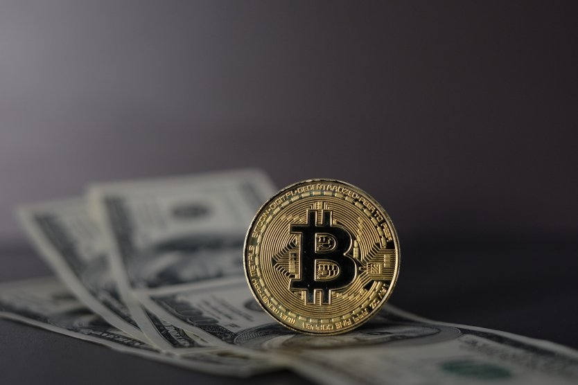 A Bitcoin sitting on top of several $100 bills