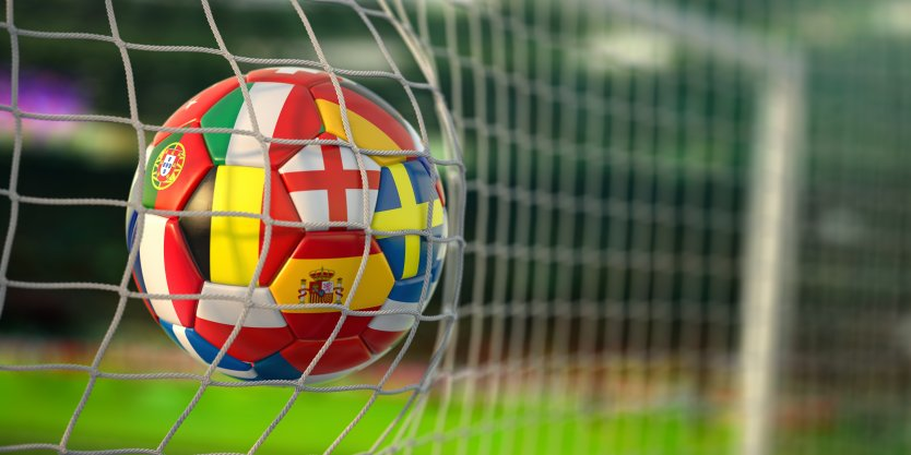 Football with flags of European countries flying into net