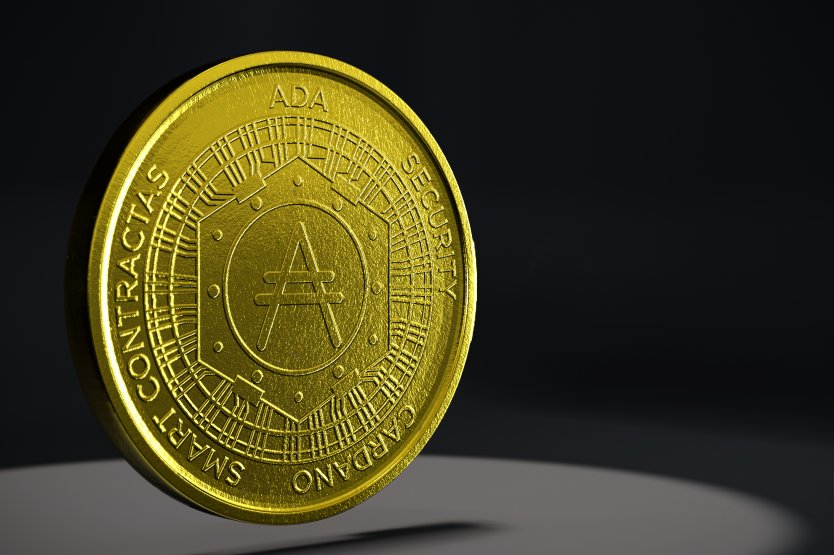 Picture of a cardano coin hovering above a grey table with a black background