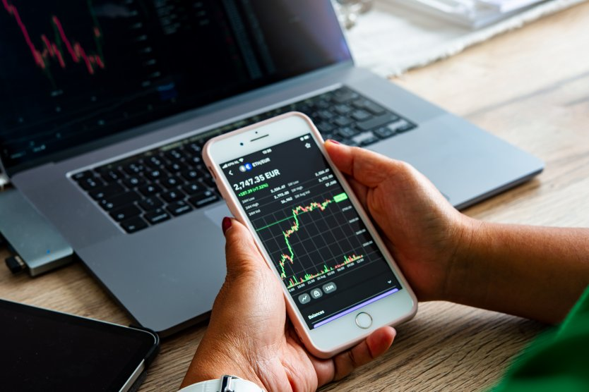 Young trader investor woman checking market chart Ethereum coin to predict market analysis price on smartphone and mobile tablet.