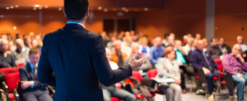 Speaker at a business conference giving a presentation to a packed conference hall.