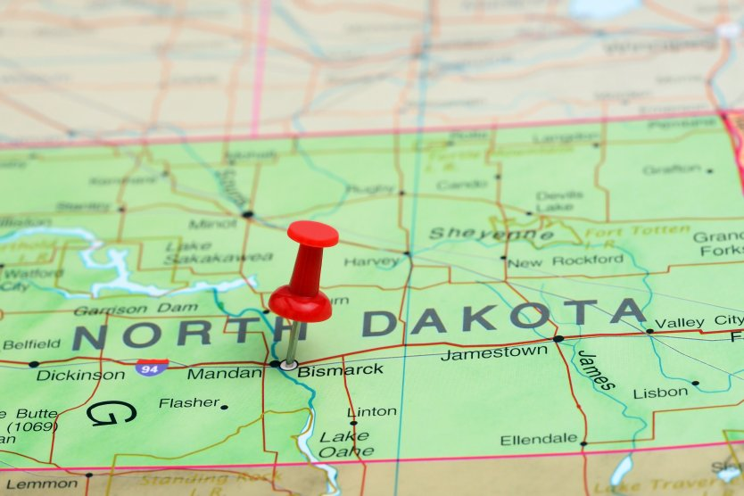 A red pin marks North Dakota on a paper USA map