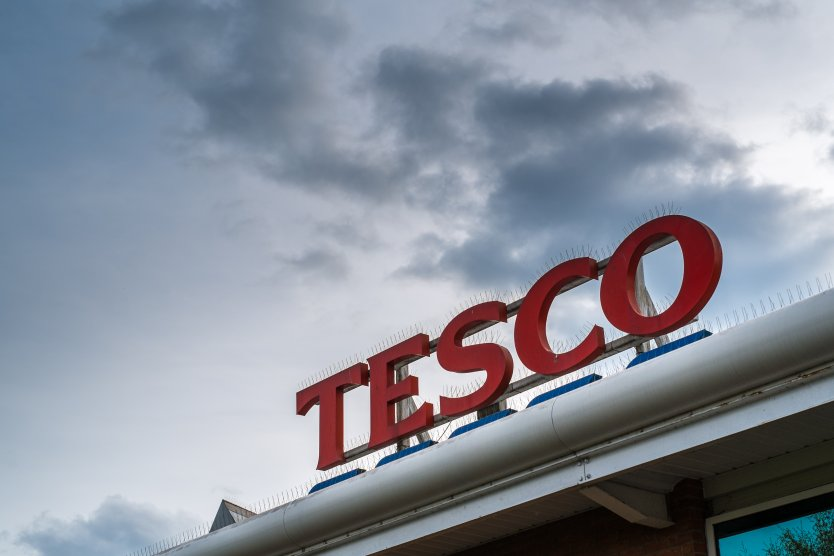 Tesco supermarket logo on top of store exterior against a moody sky in Kidderminster, UK