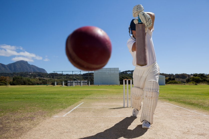 A batsman prepares to hit a cricket ball flying towards him at the wicket