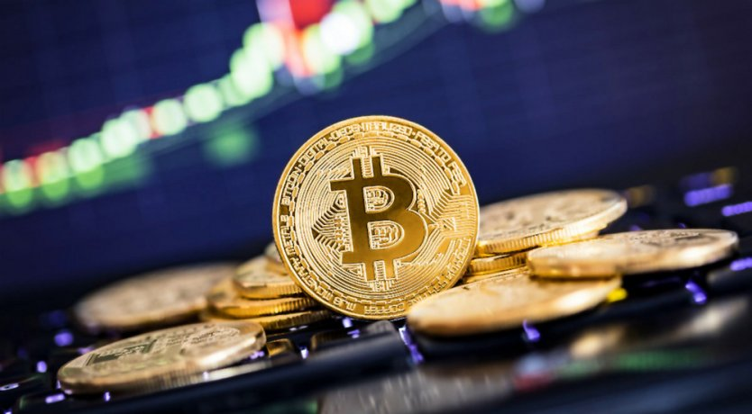 A golden bitcoin token stands on edge among other tokens in front of a blurred chart